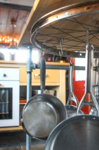 pots and pans hanging in kitchen from old upcycled bike wheel