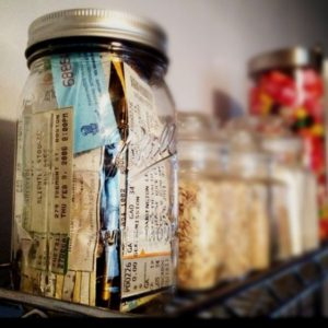mason jar filled with ticket stubs on a shelf