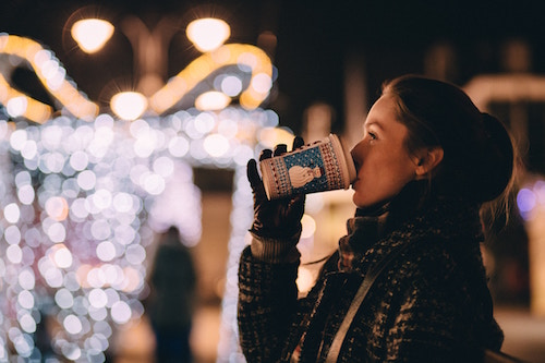 woman drinking coffee at Christmas time staring at lights