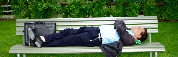 older well-dressed man napping on park bench