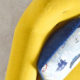 close up of arm of yellow couch with blue pillow